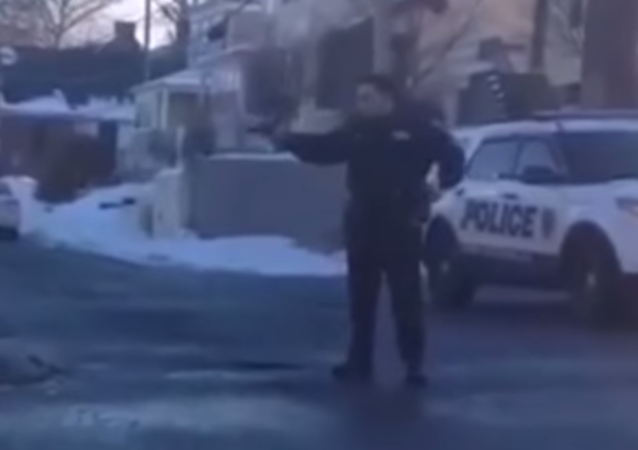 New Rochelle Police Officer points the gun at a group of teenagers having a snowball fight.