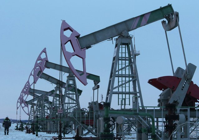 A worker walks past pump jacks on an oil field owned by Bashneft company near the village of Nikolo-Berezovka, northwest from Ufa, Bashkortostan, January 28, 2015