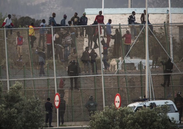 Sub-Saharan migrants sit on a metal fence that divides Morocco and the Spanish enclave of Melilla