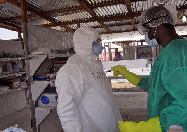 A health care worker assists a collegue inside a USAID, funded Ebola clinic in Monrovia, Liberia, Friday, Jan. 30, 2015. The World Health Organization says officials are now focused on ending the biggest-ever Ebola outbreak rather than just slowing the virus' spread. In an update published Thursday, Jan. 29, 2015, the U.N. health agency said the three most affected countries _ Guinea, Sierra Leone and Liberia _ reported fewer than 100 cases in the past week, for the first time since June, 2014.