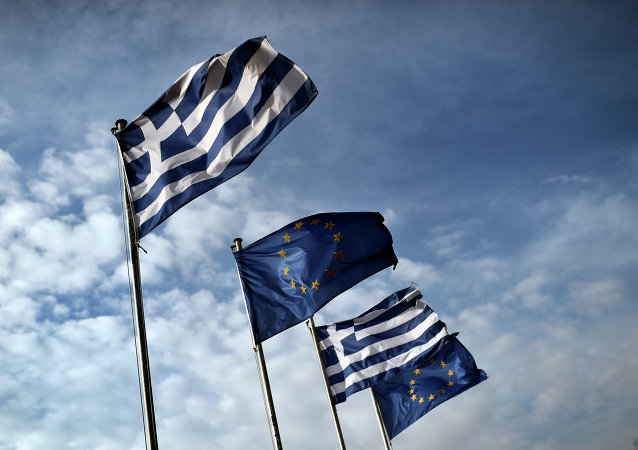 Greek and EU flags wave in the port of the eastern Greek island of Samos in January 20, 2015.