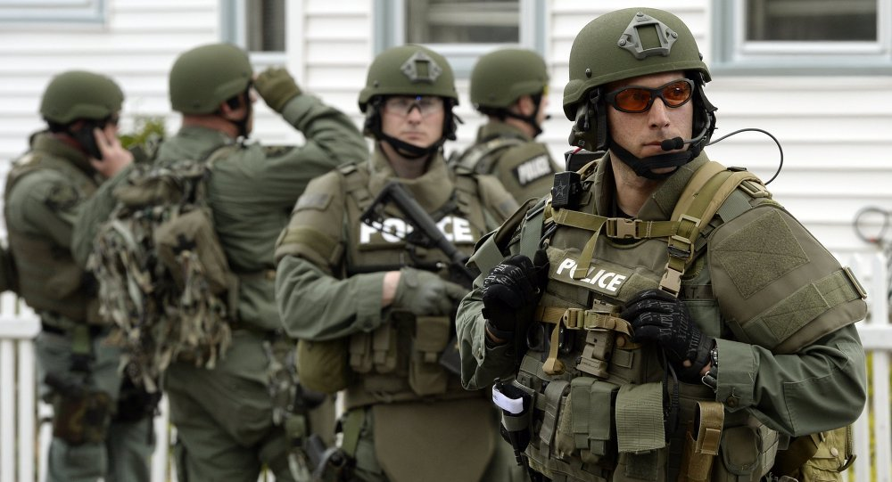 The six stand accused of sending material support, including military equipment, from the US to the Islamic State in Syria.  Above: A police SWAT team search houses for the second of two suspects wanted in the Boston Marathon bombings.
