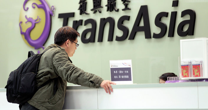A passenger waits at the ticket counter of TransAsia Airways at the Songshan Airport in Taipei, Taiwan, Saturday, Feb. 7, 2015