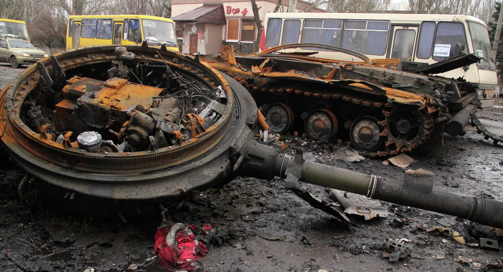Burnt military machinery in Uglegorsk. Background: a DPR bus column heading to Debaltseve for evacuation of local residents from the combat zone.