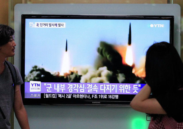People watch a TV news program showing the missile launch conducted by North Korea, at Seoul Railway Station in Seoul, South Korea, Thursday, June 26, 2014
