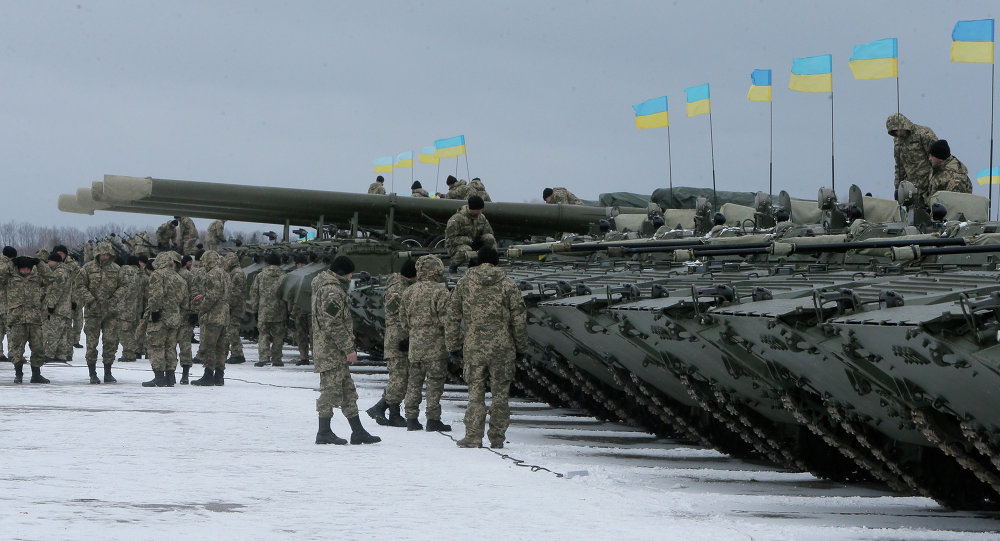 Ukrainian servicemen stand near armored vehicles during a ceremony with Ukrainian President Petro Poroshenko to mark the delivery of more than 100 pieces of military equipment to the Ukrainian armed forces, near Zhitomir, Ukraine, Jan. 5, 2015