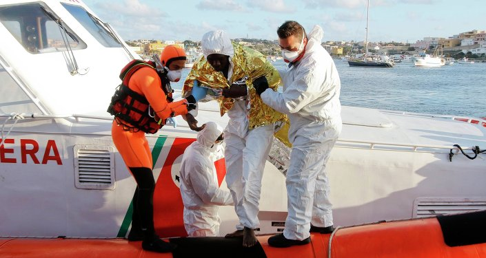 A migrant who survived a shipwreck is helped as he arrives with others at the Lampedusa harbour February 11, 2015