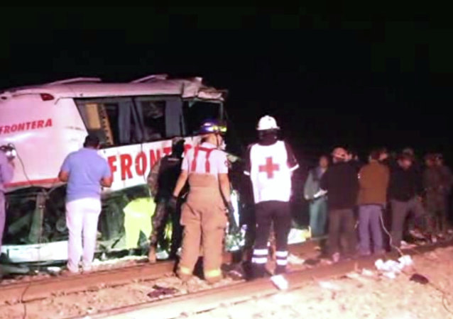 In this image made from Associated Press Television News video emergency responders work at the scene of a bus and freight train collision Friday Feb. 13, 2015. The collision at a grade crossing in northern Mexico, killed at least 16 people and injured 22, according to a Mexican official. The official said the accident Friday occured in the town of Anahuac, which is Tamaulipas state near the border city of Nuevo Laredo, across from Laredo, Texas.
