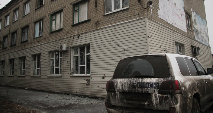 An OSCE vehicle near a house destroyed during bombardment in Debaltseve