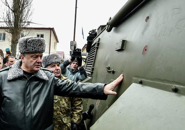Ukraine's President Petro Poroshenko inspects a British Saxon military vehicle for its bullet proof capabilities at the National Guard Training Center in Novy Petrivtsy, Ukraine, Friday, Feb. 13, 2015