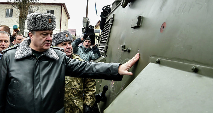 Ukraine's President Petro Poroshenko inspects a British Saxon military vehicle for its bullet proof capabilities at the National Guard Training Center in Novy Petrivtsy, Ukraine, Friday, Feb. 13, 2015
