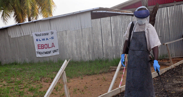 A health care worker sprays disinfectant outside a USAID, funded Ebola clinic in Monrovia, Liberia, Friday, Jan. 30, 2015