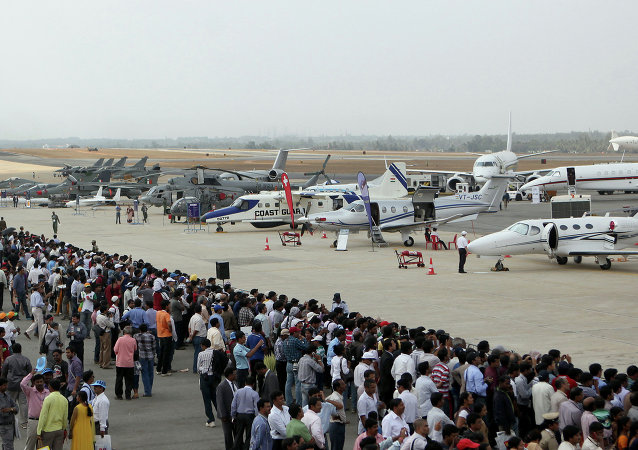 Visitors look at aircraft parked at the static display area on the third day of Aero India 2013 at Yelahanka Air Force station in Bangalore on February 8, 2013