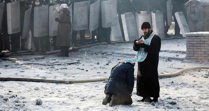 Kiev monk hearing confession during protest