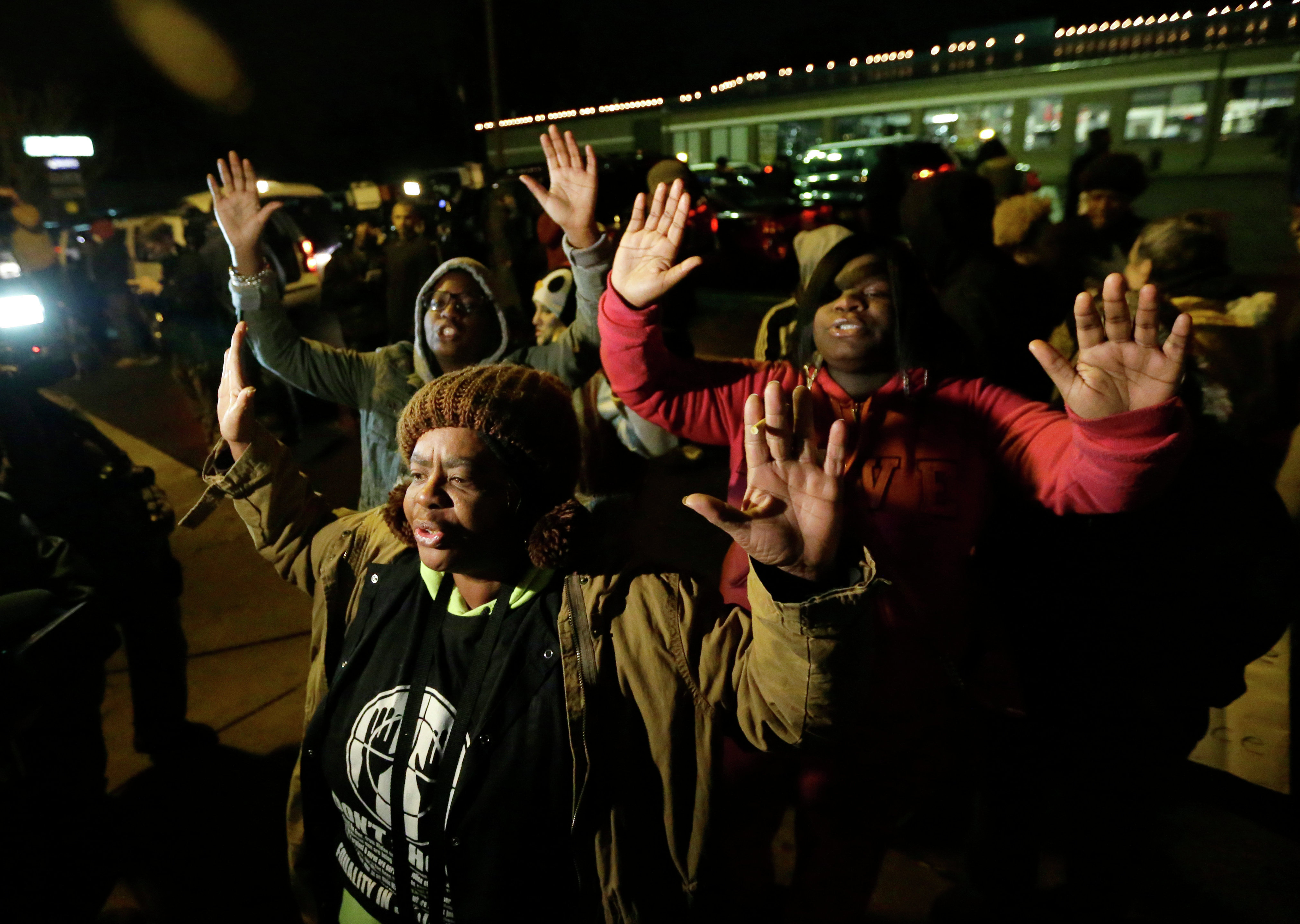 Barbara Jones, joined by other protesters, raises her hands, Monday, Nov. 24, 2014, in Ferguson, Mo., more than three months after an unarmed black 18-year-old man was shot and killed there by a white policeman. Ferguson and the St. Louis region are on edge in anticipation of the announcement by a grand jury whether to criminally charge Officer Darren Wilson in the killing of Michael Brown.