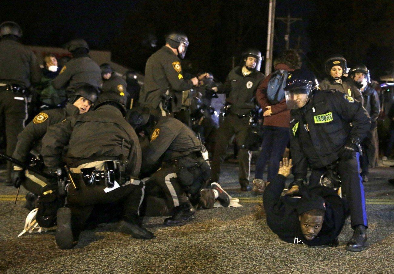 Protesters are taken into custody Friday, Nov. 28, 2014, in Ferguson, Mo.