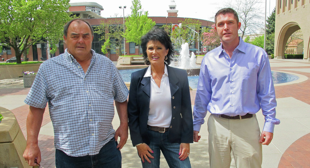Larry Harvey, Rhonda Firestack-Harvey, and Rolland Gregg stand in the plaza in front of the federal courthouse in Spokane, Wash. The three are charged with growing marijuana at a remote farm near Kettle Falls, Wash.
