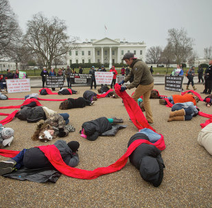 Anti-abortion activists are connected with a red piece of cloth as they stage a die-in in front of the White House.