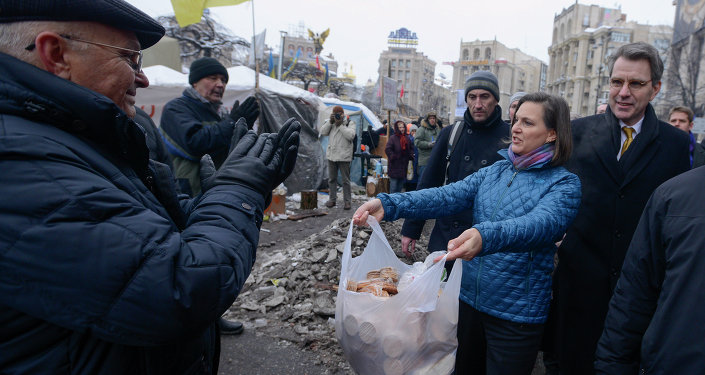 US Assistant Secretary for European and Eurasian Affairs Victoria Nuland offers food to pro-European Union activists as she and U.S. Ambassador to Ukraine Geoffrey Pyatt, right, walk through Independence Square in Kiev
