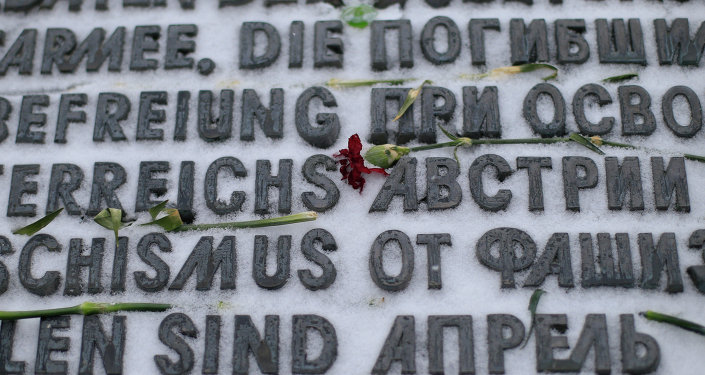 Snow covers text and flowers on the Soviet War Memorial (Heldendenkmal der Roten Armee) in Vienna