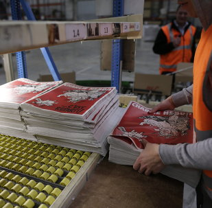 An employee checks the forthcoming edition of the weekly newspaper Charlie Hebdo, on February 24, 2015 in Villabe, south of Paris