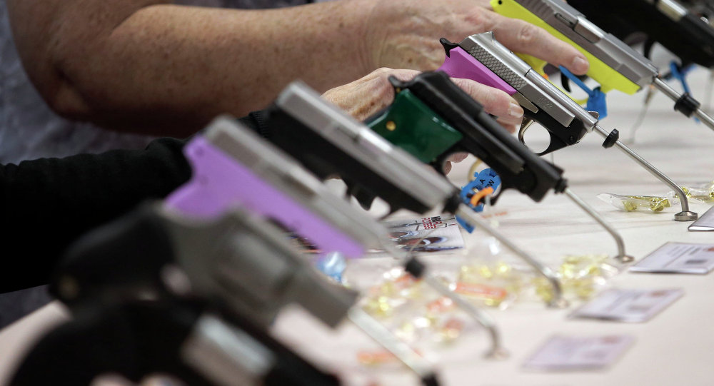 Attendees look over a pistol display at the National Rifle Association's annual convention.
