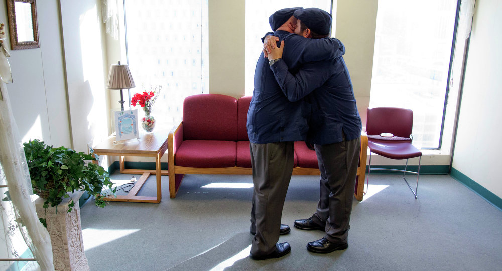 Charles Windham, left, 53, and Edgard Perez, 40, embrace after they were married at the marriage license bureau