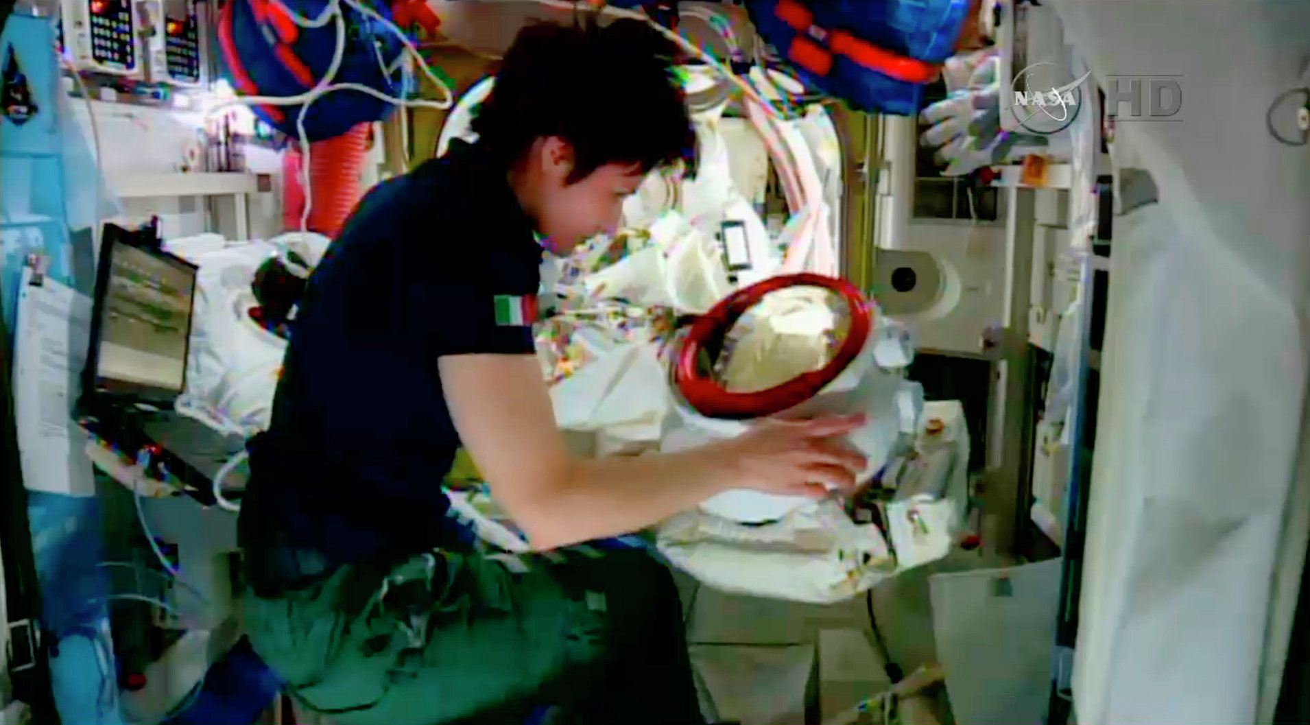 In this screenshot from a video provided by NASA, Italian astronaut Samantha Cristoforetti checks the helmet of American astronaut Terry Virts inside the International Space Station on Wednesday.