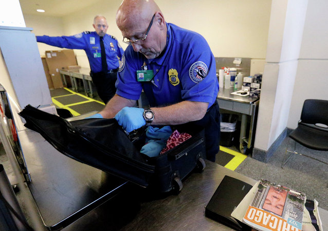 A TSA agent checks a bag at a security checkpoint area at Midway International Airport in Chicago.