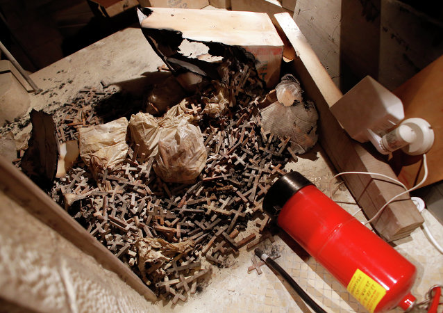 A picture taken on May 26, 2014 shows burnt wooden crosses and a fire extinguisher after arsonists set fire to a small section of the Church of the Dormition