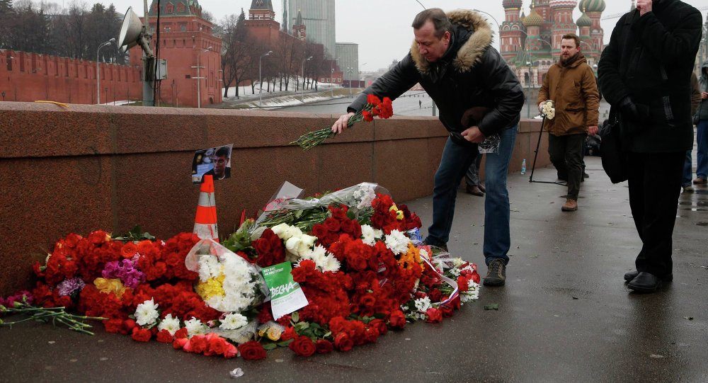 People come to lay flowers at the site, where Boris Nemtsov was shot dead, with St. Basil's Cathedral (R) and the Kremlin walls seen in the background, in central Moscow, February 28, 2015.