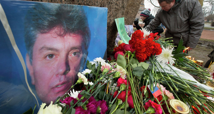 People lay flowers in memory of Boris Nemtsov, seen at left, at the monument of political prisoners 'Solovetsky Stone' in central St. Petersburg, Russia, Saturday, Feb. 28, 2015.