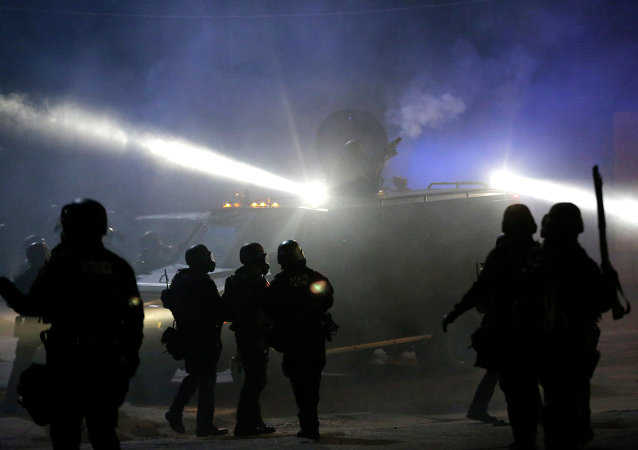 Police in riot gear stand around an armored vehicle as smoke fills the streets Tuesday, Nov. 25, 2014, in Ferguson, Mo.