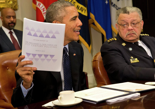 Philadelphia Police Commissioner Charles Ramsey watches at right as President Barack Obama holds up a copy of the interim report of the President's Task Force on 21st Century Policing.