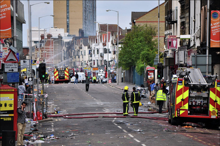 Croydon road looking like a tornado swept up it as fire tenders spray water twelve hours after the fires were set during riots in 2011.