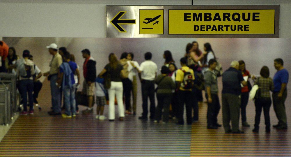 People queue with their luggage at the departure area of the Maiquetia international airport that serves Caracas on July 3, 2014