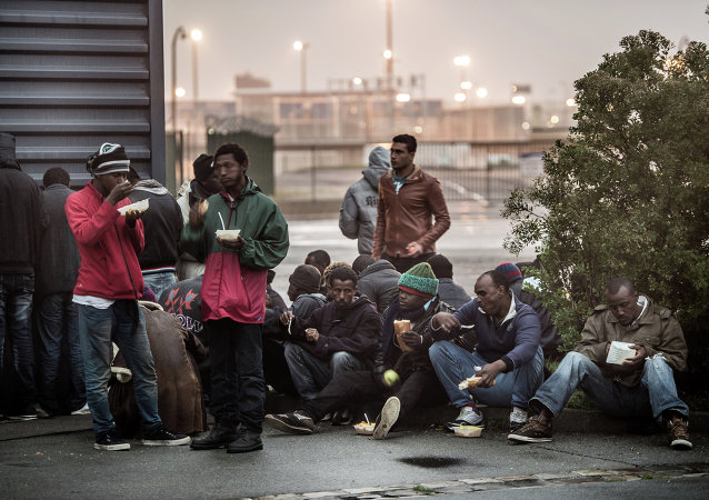 Migrants eat hot meals served by humanitarian organizations in the northeastern French port of Calais on October 29, 2014