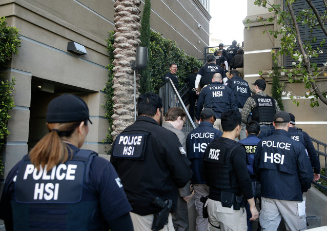 Federal agents enter an upscale apartment complex, Tuesday, March 3, 2015, in Irvine, Calif.