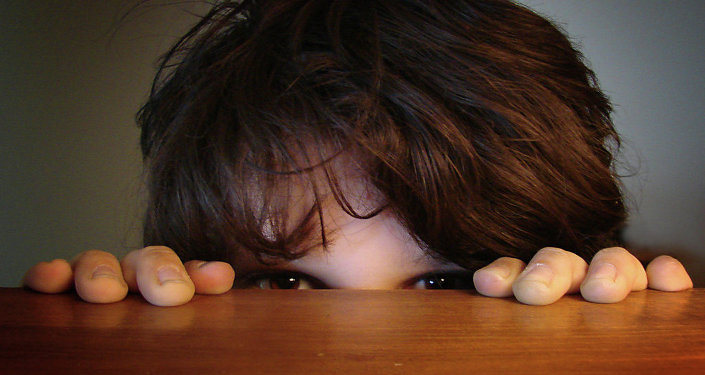 A child hiding behind the table
