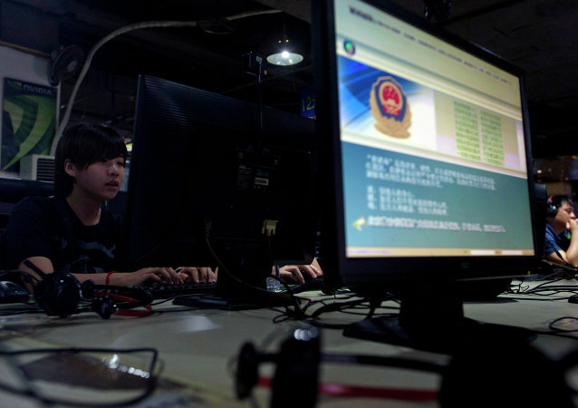 In this Aug. 19, 2013 file photo, computer users sit near a monitor display with a message from the Chinese police on the proper use of the Internet at an Internet cafe in Beijing, China