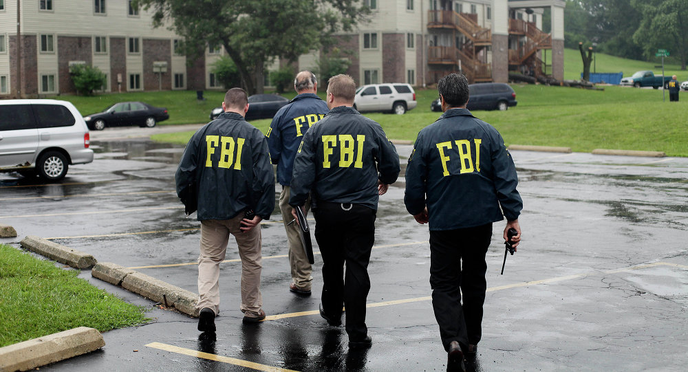 FBI Agents on August 16, 2014, investigate the shooting death of 18-year-old Michael Brown at the location where he was killed on Canfield Drive in Ferguson, Missouri