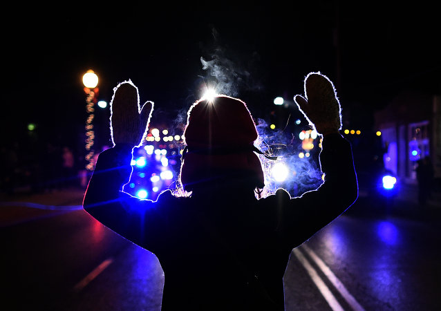 This November 25, 2014 file photo shows a protester holding up her hands in front of a police car in Ferguson