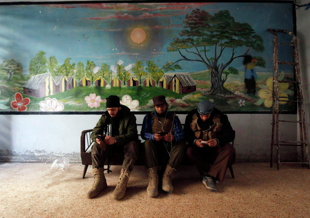 Rebel fighters of 'Al-Sultan Murad' brigade use their mobile phones inside a room near the frontline in Handarat area, north of Aleppo March 1, 2015