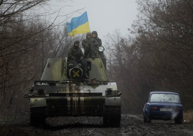 Ukrainian servicemen ride atop an armored vehicle with a Ukrainian flag, on the outskirts of Donetsk, Ukraine
