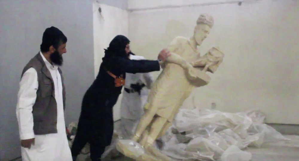 In this image made from video posted on a social media account affiliated with the Islamic State group on Thursday, Feb. 26, 2015, which has been verified and is consistent with other AP reporting, a militant topples an ancient artifact in the Ninevah Museum in Mosul, Iraq
