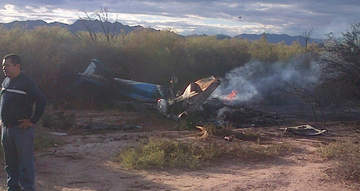 A man stands near one of two helicopters that crashed near Villa Castelli in the La Rioja province of Argentina, Monday, March 9, 2015