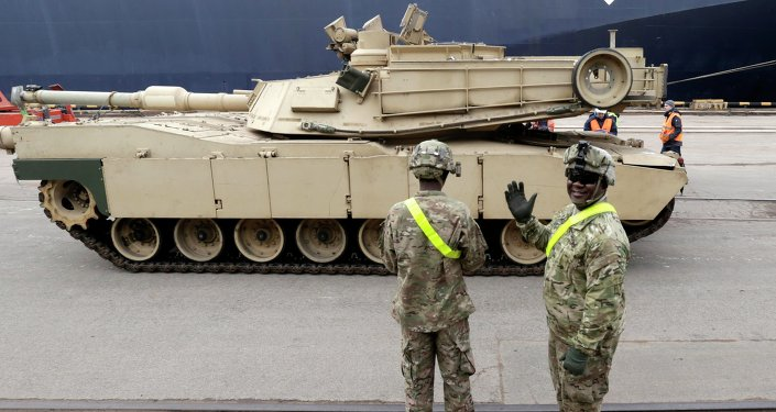 A US soldier greets the media as custom officers inspect an Abrams main battle tank, for US troops deployed in the Baltics as part of NATO's Operation Atlantic Resolve