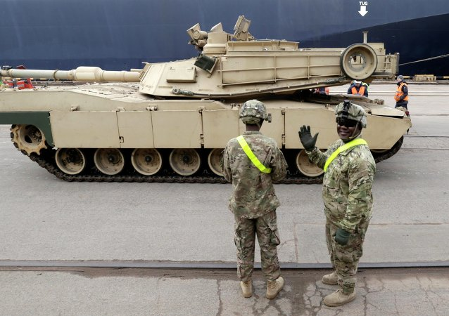 A U.S. soldier greets the media as custom officers inspect an Abrams main battle tank, for U.S. troops deployed in the Baltics as part of NATO's Operation Atlantic Resolve