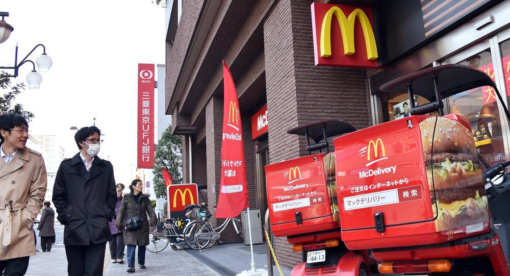 Pedestrians walk past a McDonald's fast-food restaurant in Tokyo on January 9, 2015