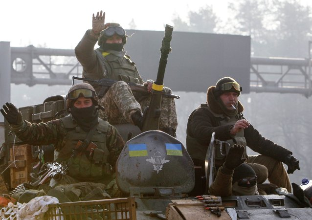 Ukrainian servicemen ride atop an armoured personnel carrier (APC), as they return from the frontline in eastern Ukraine, in Kiev March 11, 2015